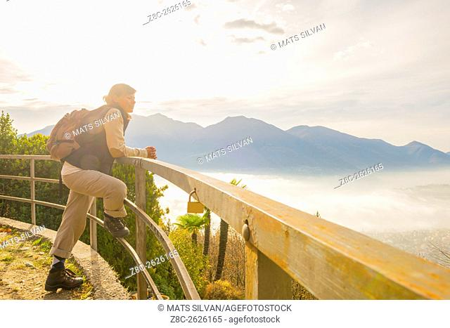 Woman with backpack leaning on a railing and enjoy panoramic view with sea of fog over alpine lake Maggiore with mountain in Ticino, Switzerland