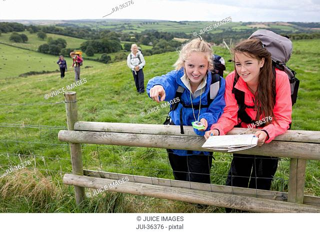 Portrait of smiling girls with backpacks compass and map pointing in field