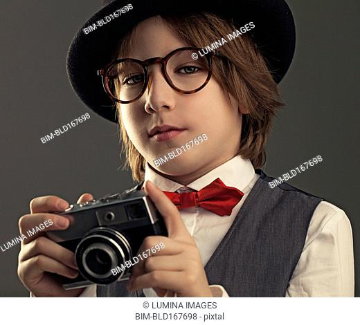 Close up of boy in hat photographing with vintage camera