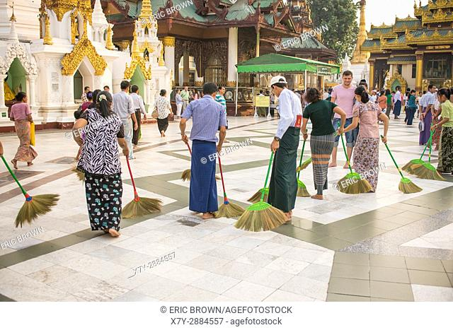 Cleaning the floor with the softest brooms ever. Shwedagon Pagoda, Yangon, Myanmar