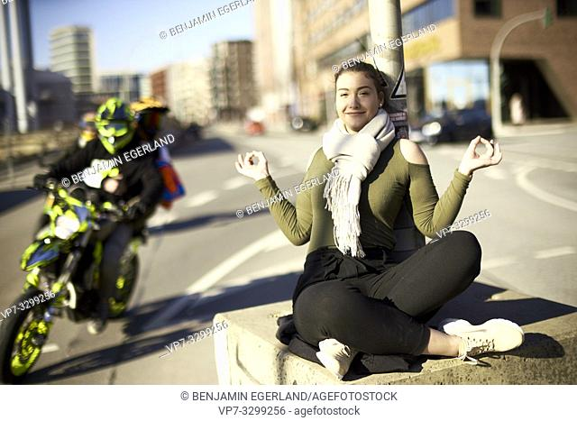 relaxed woman meditating in middle of street next to traffic, in Hamburg, Germany