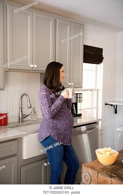 Pregnant woman standing in kitchen and holding mug