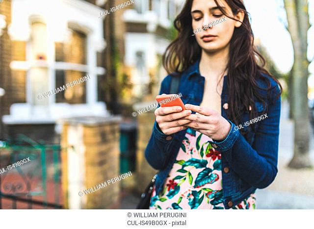 Young woman walking down street, looking at smartphone