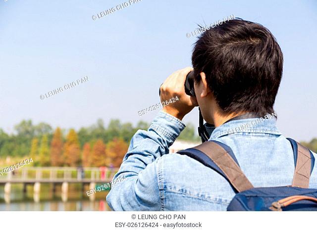 The back rear of man using binoculars