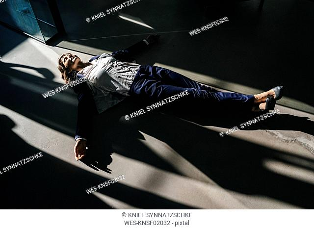 Businesswoman lying on floor in office