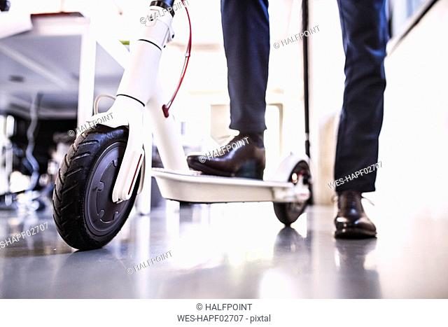 Close-up of businessman with scooter in office