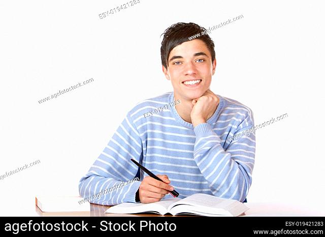 Young happy handsome male student sitting on desk learning for e