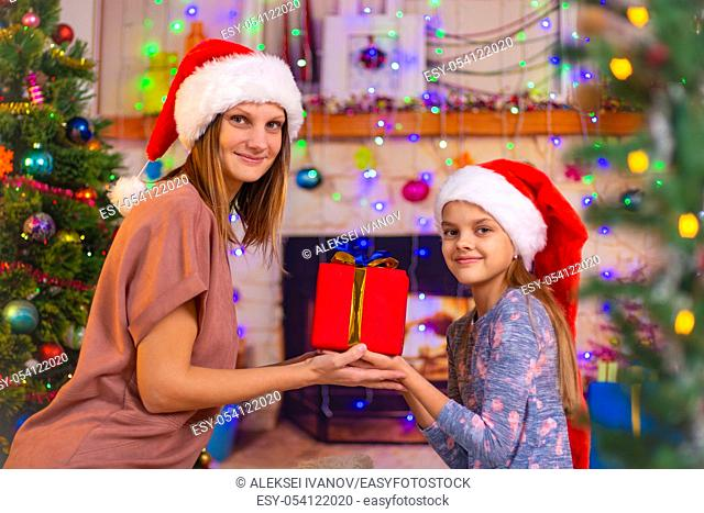 Mom and daughter hold a gift and looked into the frame