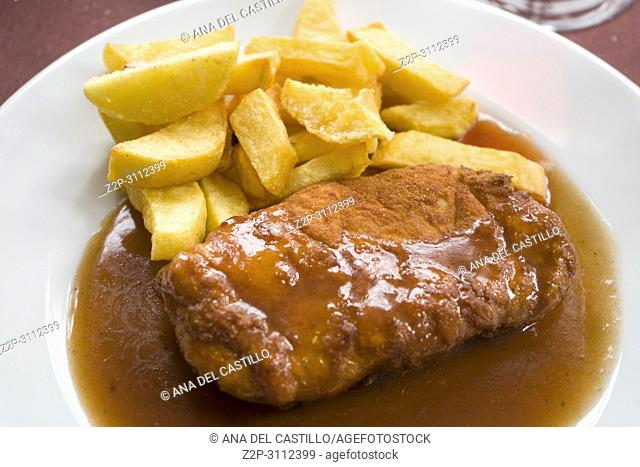 Milanese pork meat with fries on plate