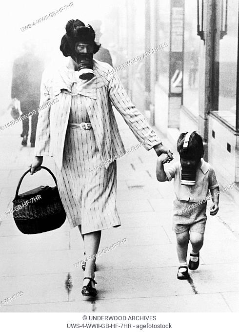 London, England: September 12, 1941.A woman shopper and her child wearing gas masks pass through a gas drill area in Wembley