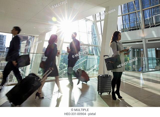 Business people with suitcases walking and standing in sunny airport atrium