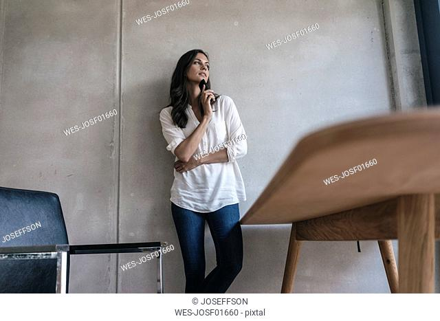 Thoughtful woman with cell phone at concrete wall