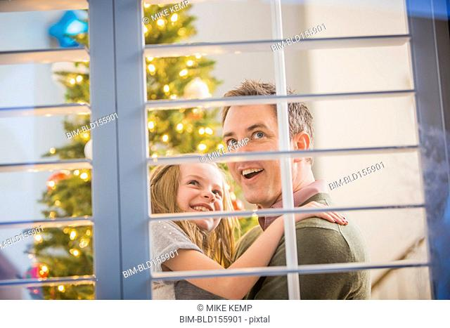 Caucasian father and daughter looking for Santa at Christmas