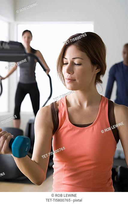 Three people exercising in gym
