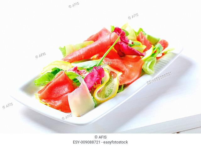 Green salad with thin slices of lemon and raw beef