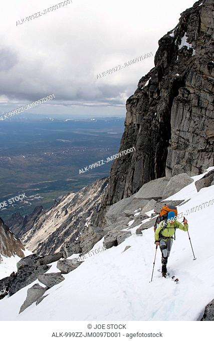 View of female skier by granite cliffs above the Swift River at the south end of the Revelation Mountains, Summer in Southcentral Alaska