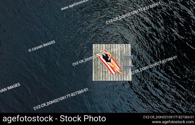 Aerial of woman relaxing alone on floating dock on lake in summer