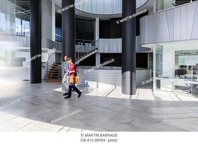 Businessmen walking in modern office lobby