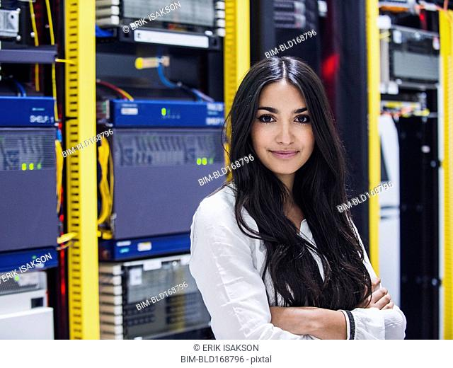 Mixed race technician smiling in server room