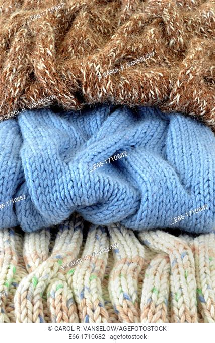 stack of knitted cabled cowls: from alpaca, wool and cotton