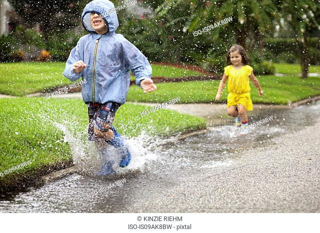 Boy and sister wearing rubber boots running and splashing in rain puddle