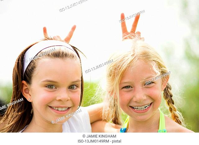 2 young girls smiling giving rabbit ears