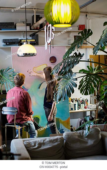 Artists discussing large painting in apartment