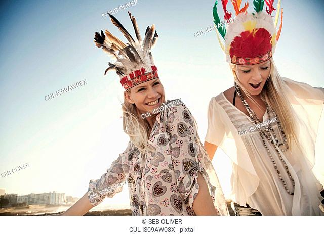 Young women wearing feather headdresses dancing in sunlight, looking at camera smiling
