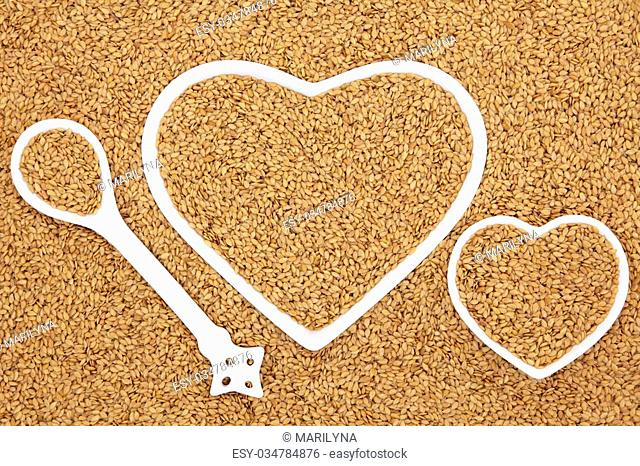 Golden flax seed health food in heart shaped porcelain bowls and spoon forming an abstract background