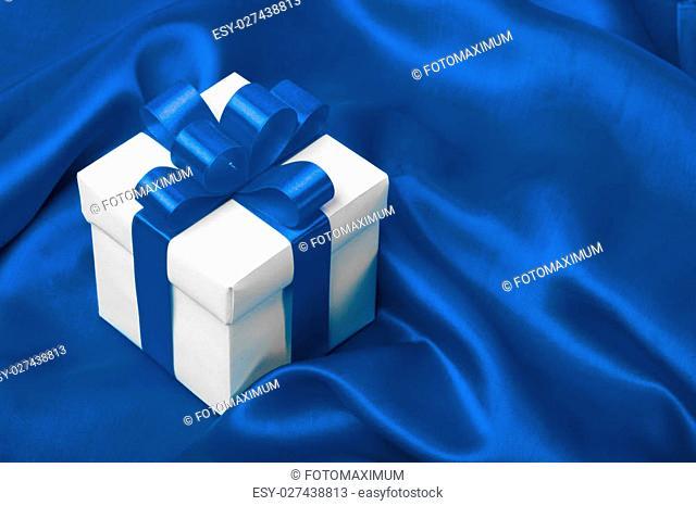 gift on blue satin background. studio shot