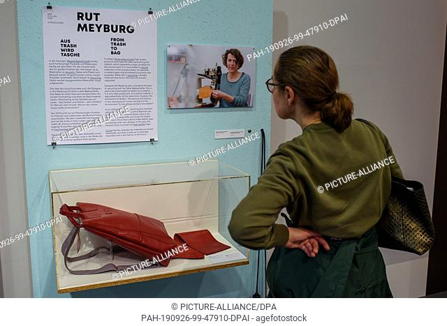 26 September 2019, Berlin: A visitor looks at a display board about the project of the artist Rut Meyburg, who recycles old leather sofas into bags
