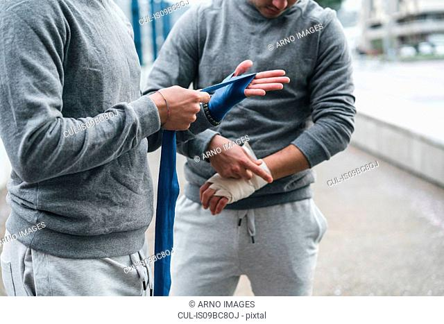 Male adult twin boxers training outdoors, bandaging hands with hand wraps, mid section
