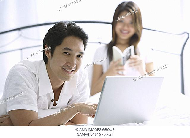 Couple in bedroom, man using laptop, looking at camera