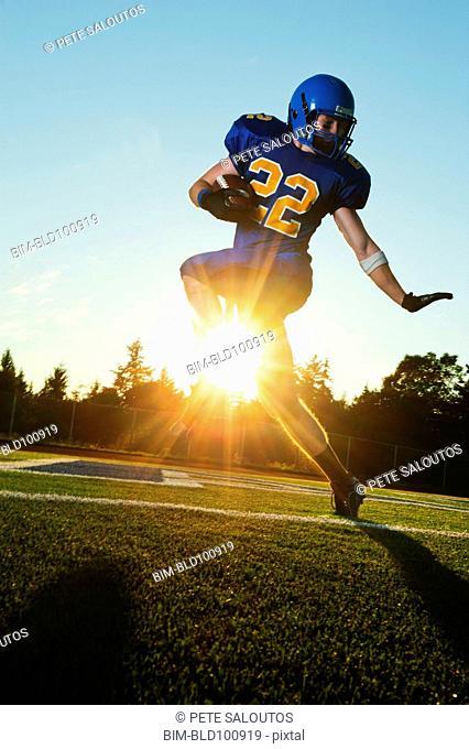 Caucasian football player running with ball