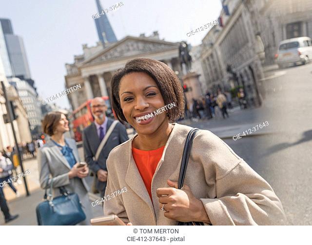 Portrait smiling, confident businesswoman on urban city street, London, UK
