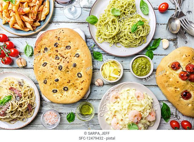 Table with several plates of pasta with different kinds of sauce and focaccia bread (Italian food)