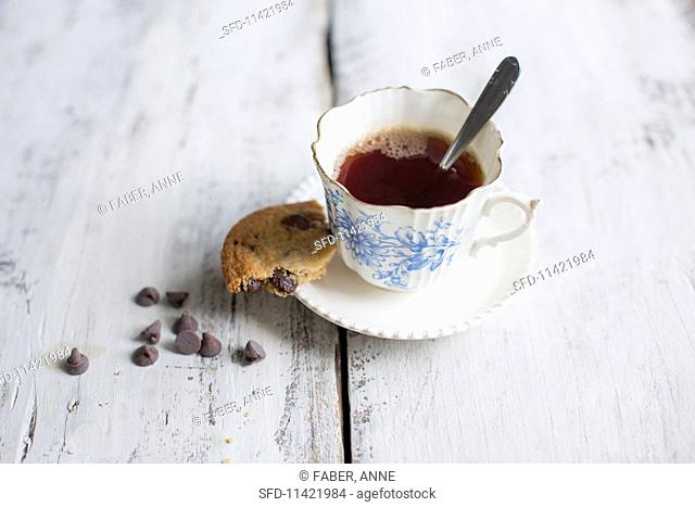 A chocolate chip cookie with a cup of tea
