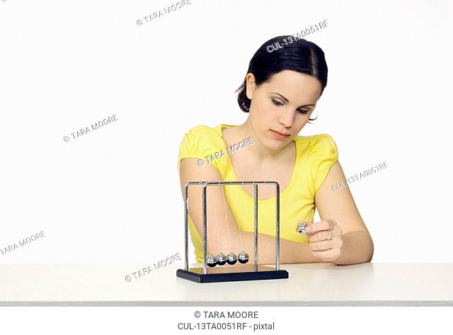 woman playing with newton's cradle