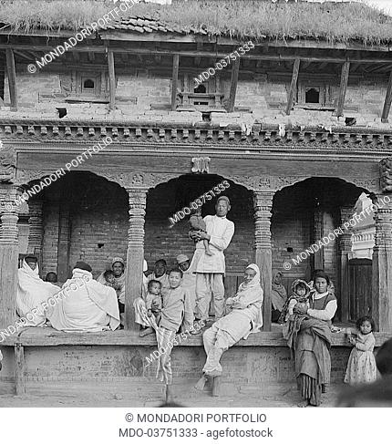 Nepalese gathered under the porch of a building. Nepal, 1965