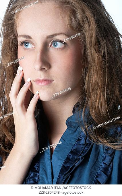 Worried young woman hand touching face looking away