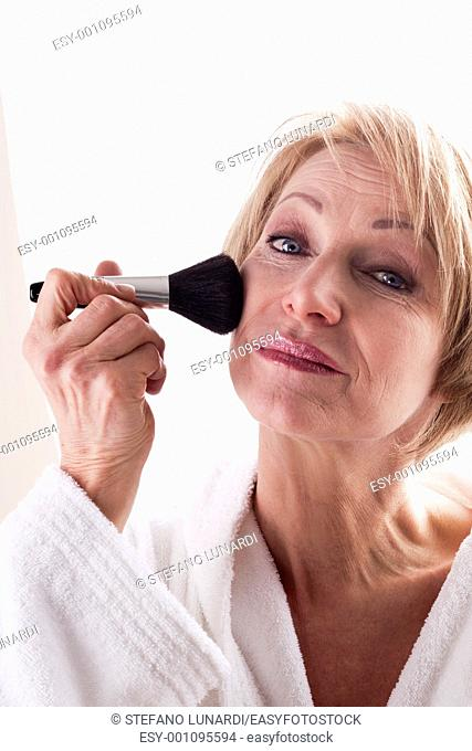 Mature Woman applying face powder