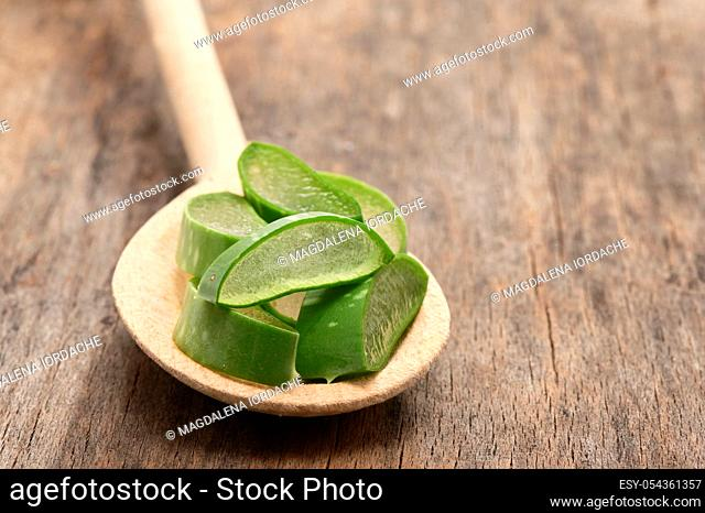 Aloe Vera Slices And Spoon on Wooden Table