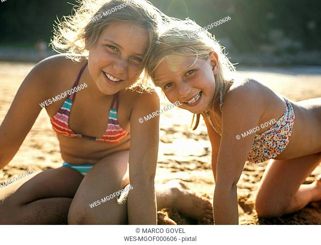 Portrait of two sisters head to head on the beach