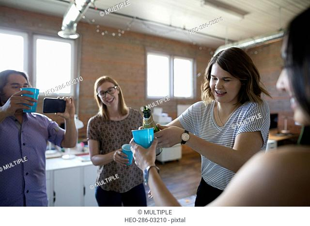 Creative business people celebrating pouring champagne in office