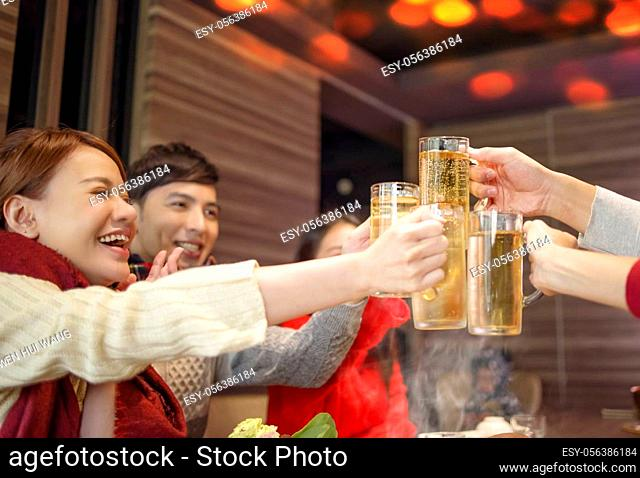 happy friends drinking and toasting beer at hot pot restaurant