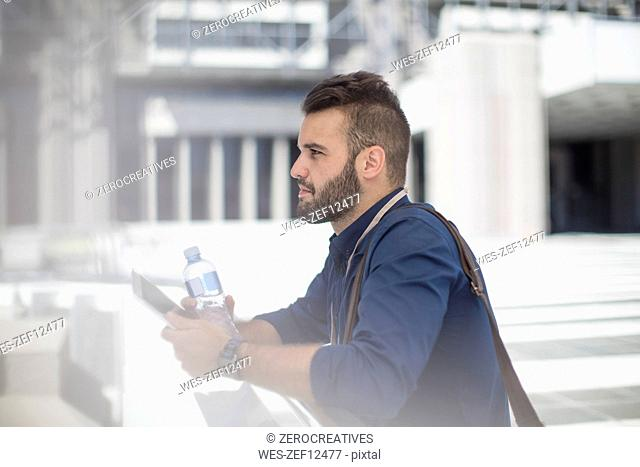 Young man with tablet and bottle of water outdoors