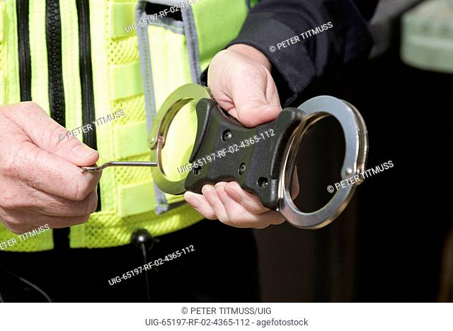 Close up of police officer holding the key to a pair of handcuffs