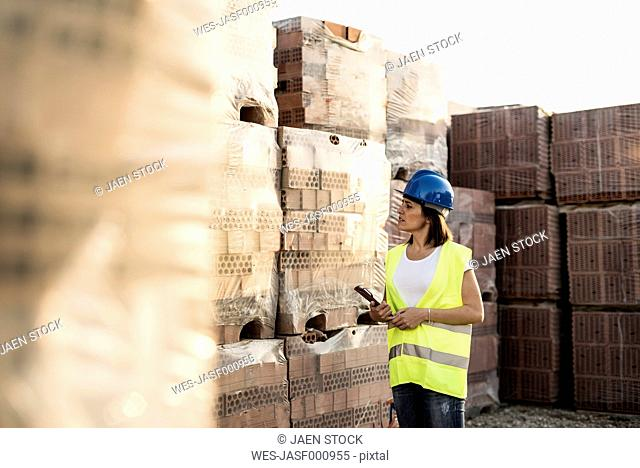 Female construction worker checking building materials