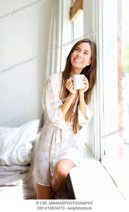 Woman smiling by window drinking tea