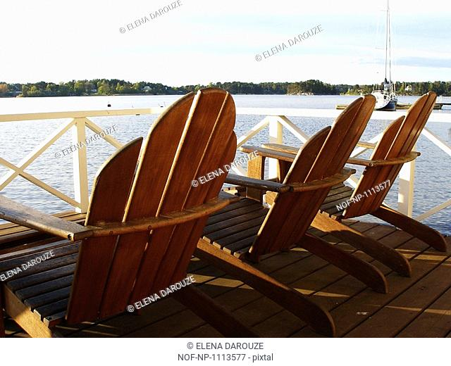 Wooden deck chairs by the sea, Sweden